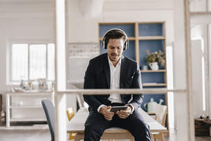 Businessman with tablet and headphones sitting on tableの写真素材 [FYI04346743]