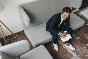 Smiling businessman with notebook on couchの写真素材 [FYI04346744]