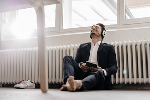 Businessman with tablet and headphones sitting on floorの写真素材 [FYI04346745]