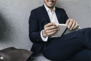 Smiling businessman with notebook on couchの写真素材 [FYI04346762]