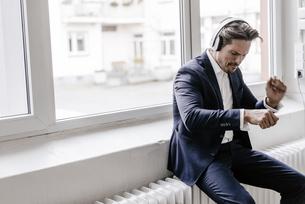Passionate businessman listening to music on headphonesの写真素材 [FYI04346771]