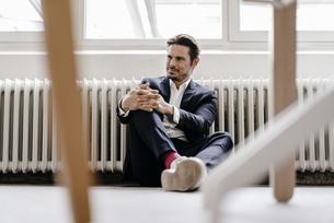 Smiling businessman sitting on the floorの写真素材 [FYI04346781]