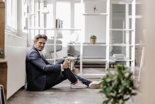 Smiling businessman sitting on the floorの写真素材 [FYI04346783]