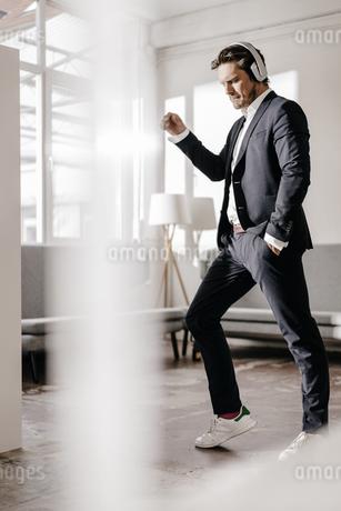 Passionate businessman listening to music on headphonesの写真素材 [FYI04346791]