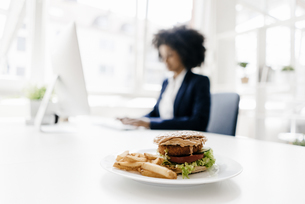Young businesswoman working with hamburger on her deskの写真素材 [FYI04346837]