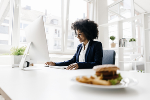 Young businesswoman working with hamburger on her deskの写真素材 [FYI04346838]