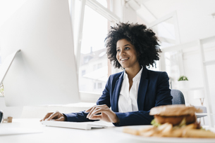 Young businesswoman working with hamburger on her deskの写真素材 [FYI04346839]