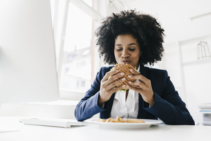 Young businesswoman eating hamburger at her deskの写真素材 [FYI04346840]