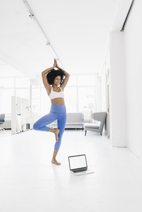 Young woman practising yoga with laptop by her sideの写真素材 [FYI04346860]