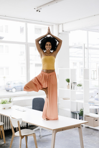 Young woman doing yoga on her deskの写真素材 [FYI04346874]