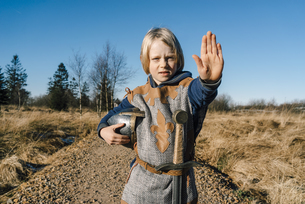 Portrait of little boy wearing knight costume in natureの写真素材 [FYI04346900]