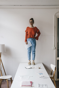 Young woman standing on table thinkingの写真素材 [FYI04346953]