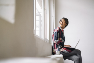 Smiling woman sitting at the window using laptopの写真素材 [FYI04346970]