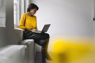 Woman sitting at the window using laptopの写真素材 [FYI04346990]