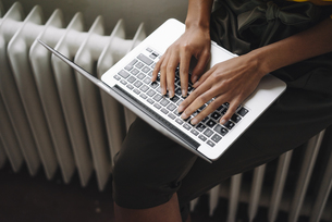 Woman sitting on heater using laptopの写真素材 [FYI04346993]