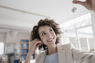 Businesswoman in office holding disco balls on her earsの写真素材 [FYI04347064]