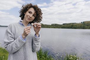 Woman at lake plucking daisy's petalsの写真素材 [FYI04347075]