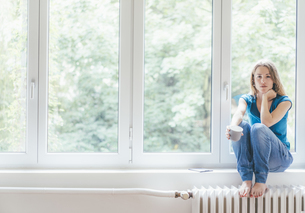 Portrait of young woman sitting at the window holding cupの写真素材 [FYI04347095]