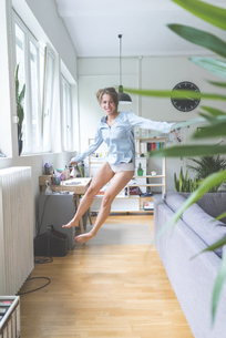 Excited young woman jumping at homeの写真素材 [FYI04347110]