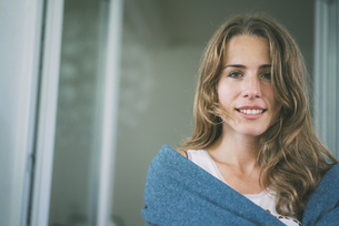 Portrait of smiling young woman wrapped in a blanketの写真素材 [FYI04347123]