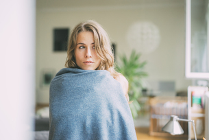 Portrait of young woman wrapped in a blanketの写真素材 [FYI04347156]