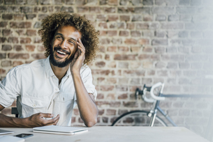 Happy young man at deskの写真素材 [FYI04347174]