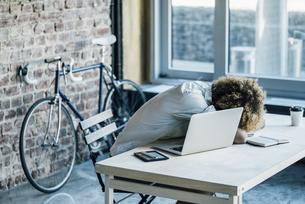 Young man lying on deskの写真素材 [FYI04347200]
