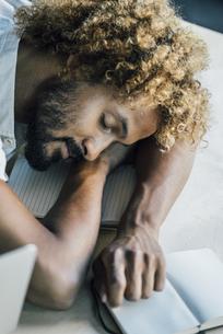 Young man lying on desk sleepingの写真素材 [FYI04347201]