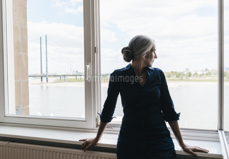 Businesswoman looking out of window in waterfront officeの写真素材 [FYI04347209]