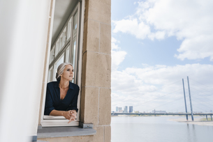 Businesswoman looking out of window in waterfront officeの写真素材 [FYI04347212]