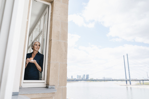 Businesswoman looking out of window in waterfront officeの写真素材 [FYI04347214]