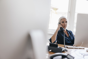 Businesswoman on the phone in officeの写真素材 [FYI04347215]