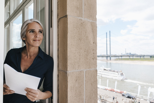 Smiling businesswoman looking out of window in waterfront ofの写真素材 [FYI04347217]