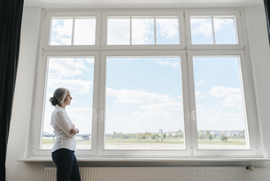 Businesswoman in office looking out of windowの写真素材 [FYI04347224]