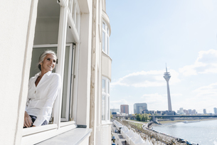 Businesswoman looking out of window in waterfront officeの写真素材 [FYI04347229]