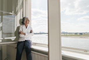 Businesswoman in office looking out of windowの写真素材 [FYI04347232]