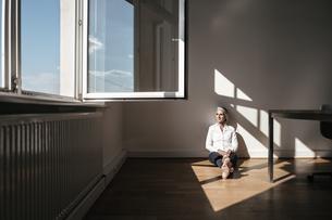 Businesswoman sitting on floor in officeの写真素材 [FYI04347234]