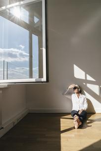 Businesswoman sitting on floor in officeの写真素材 [FYI04347235]