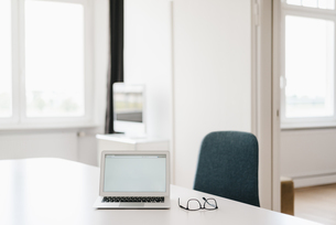 Laptop and glasses on table in officeの写真素材 [FYI04347242]