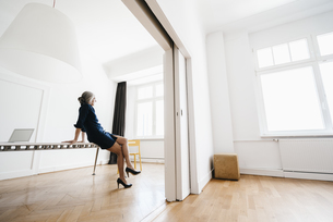 Businesswoman sitting on table in modern officeの写真素材 [FYI04347244]