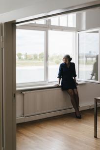 Businesswoman sitting on windowsillの写真素材 [FYI04347246]