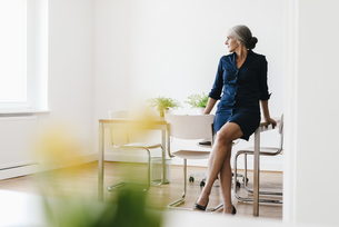 Businesswoman sitting on table in modern officeの写真素材 [FYI04347247]