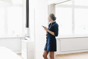 Businesswoman in office looking out of windowの写真素材 [FYI04347249]