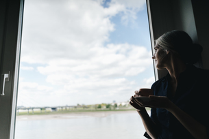 Businesswoman looking out of window in waterfront officeの写真素材 [FYI04347250]