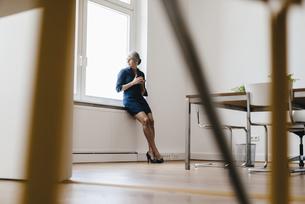 Businesswoman sitting on windiwsillの写真素材 [FYI04347252]