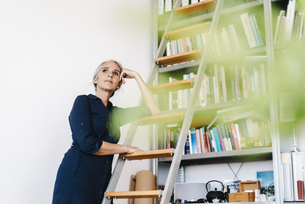 Businesswoman in office leaning against a ladderの写真素材 [FYI04347253]