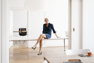 Smiling businesswoman sitting on table in modern officeの写真素材 [FYI04347254]
