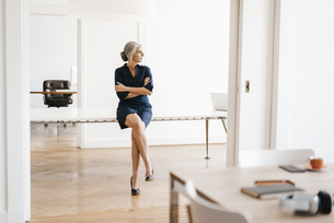 Businesswoman sitting on table in modern officeの写真素材 [FYI04347255]