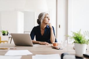 Businesswoman working on laptop in officeの写真素材 [FYI04347256]