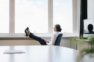 Businesswoman in office sitting at the window looking outの写真素材 [FYI04347257]
